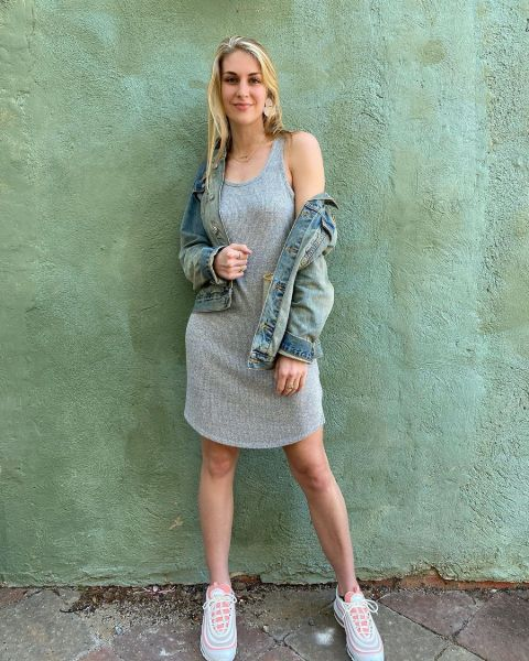 Cassidy Hallow in a grey dress poses for a picture.