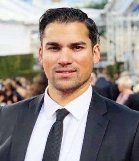 Keyan Safyari in a black suit poses for a picture.