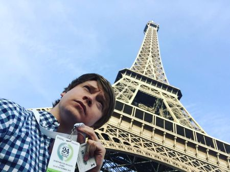 Calum Worthy in front of Eiffel Tower