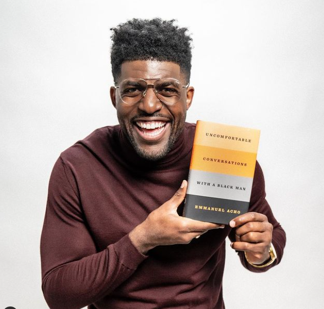Emmanuel Acho Holding Book 'Uncomfortable Conversations with a Black Man'