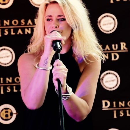 Kate DeAraugo singing at a red carpet event.
