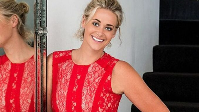Kate DeAraugo wearing a red dress and posing for a photo.